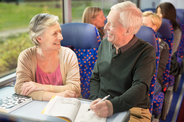 Elder couple doing cross word on coach and relaxing, Stagecoach, Megabus | by McAteer Photograph