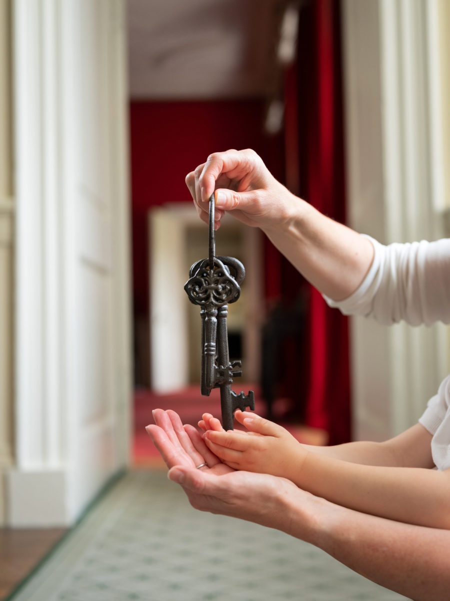 Child and mother holding a large old key | Image by McAteer Photo