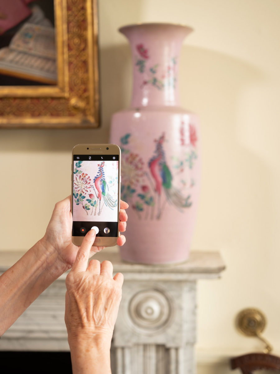 Older women taking photographs of a pink vase with her mobile phone | Image by McAteer Photo