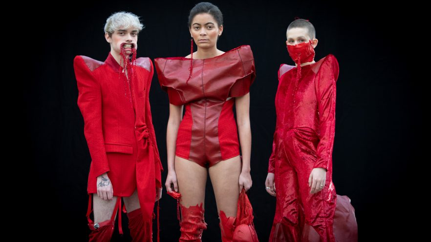Three models dressed in red on the catwalk. The event is the Glasgow School of Art's second and third year Fashion Design and Textiles show at the Briggait in Glasgow's Saltmarket district. | Images by mcAteer Photo